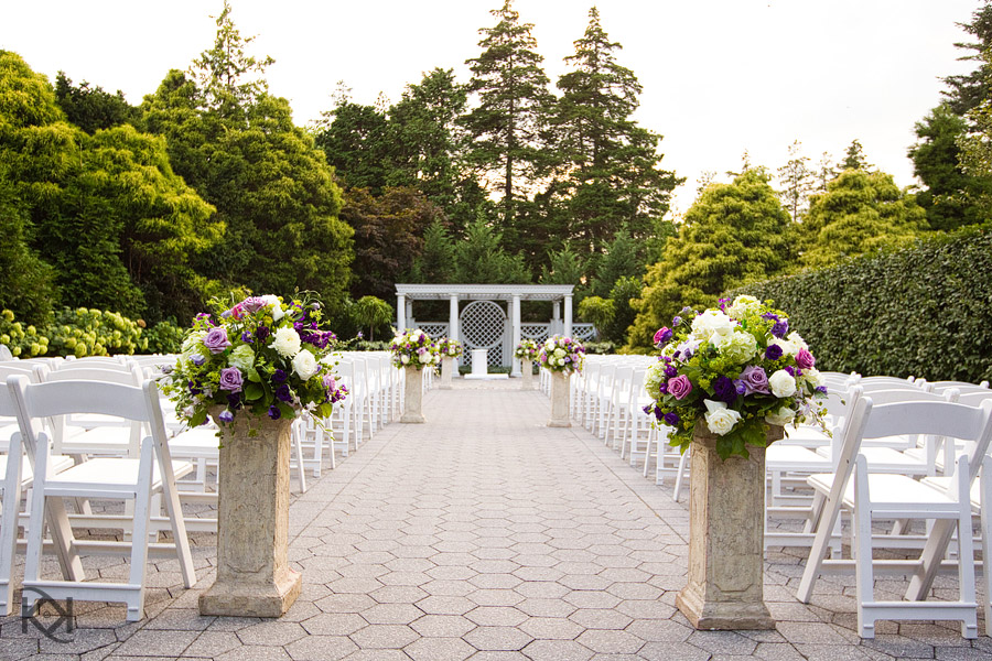 outdoor garden weddings- formal garden setting with white chairs, pillars for flowers, and and white wedding backdrop