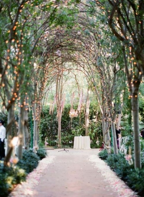 outdoor garden weddings- arched trees with lights form a canopied aisle