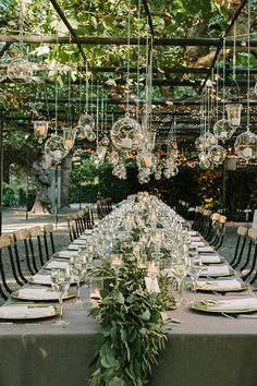 outdoor garden weddings-long table for dinner with glass lights hanging from above