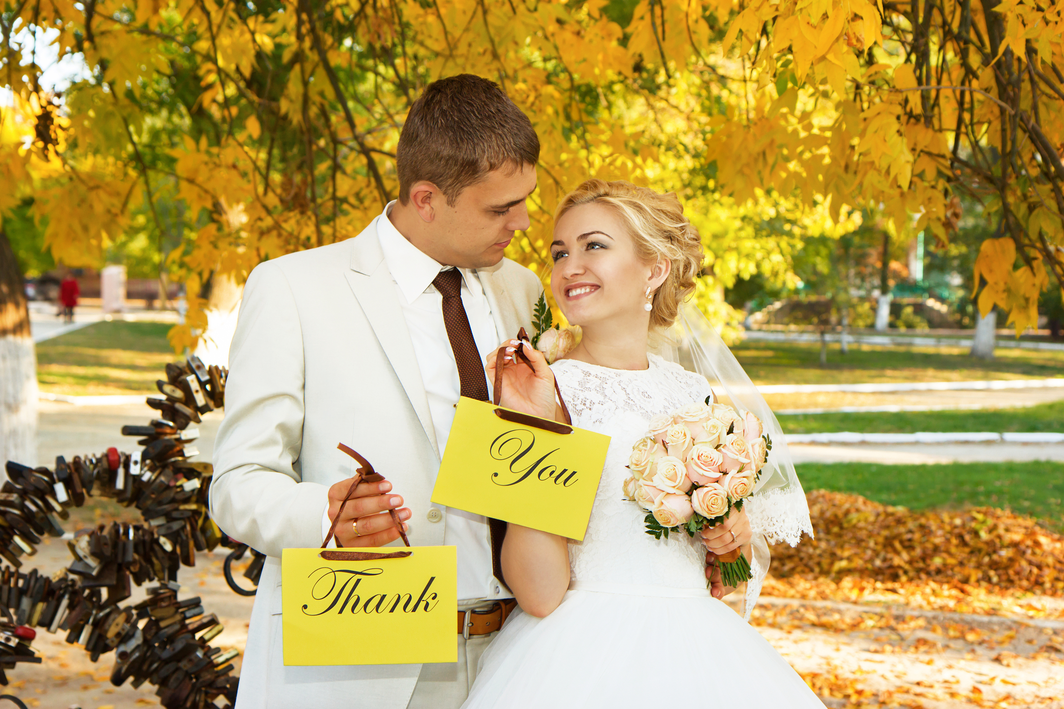 couple holding wedding thank you signs-wedding thank you card wording