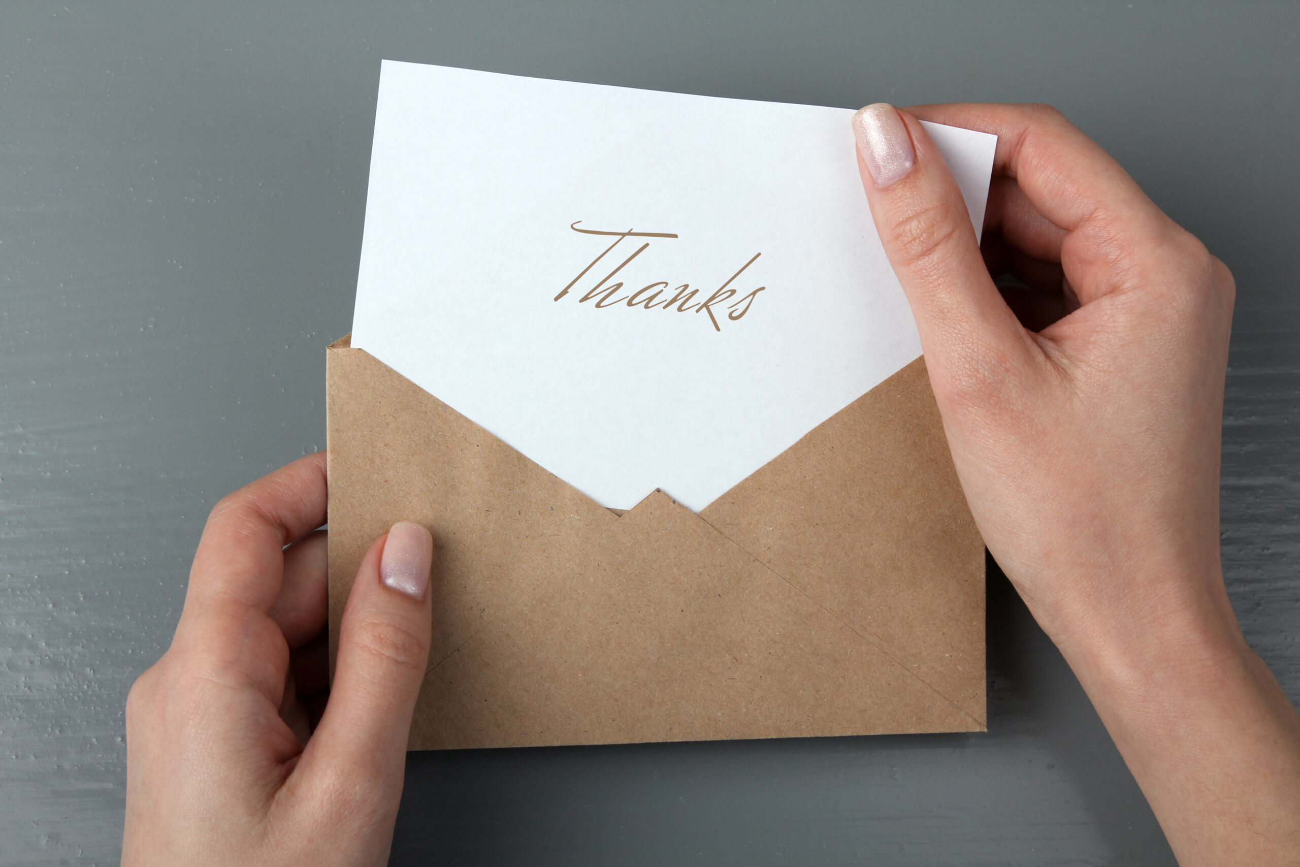 wedding thank you card wording-person pulling thank you card out of envelope